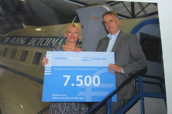 De Stichting Vrienden van WKV Roda ontvangt 7.500,- euro van het Schipholfonds. Op de vliegtuigtrap van de Dakota neemt voorzitter Age Knossen de cheque in ontvangst.