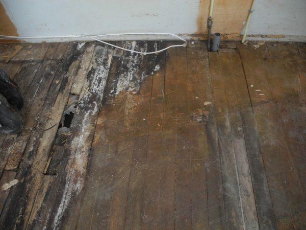De verrotte vloer in de keuken.
